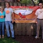 Kent Antonius and Family Posing In Front of Sausagefest Banner