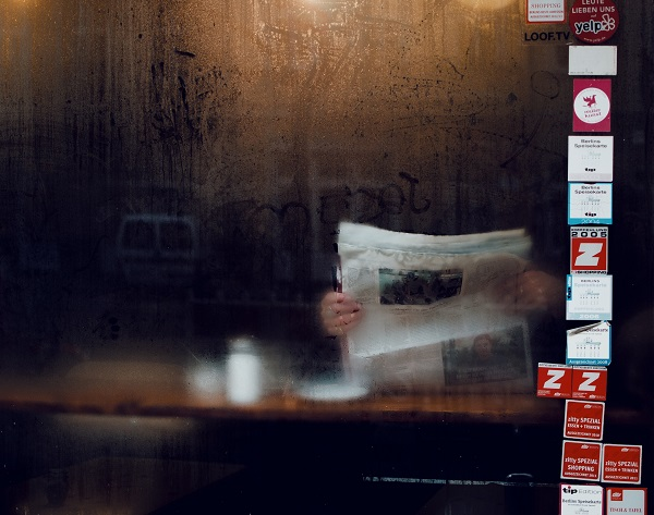 Person obscured by the newspaper they are reading